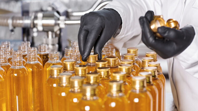 Laboratory scientist in black rubber gloves screwing caps of transparent plastic bottles filled with shampoo